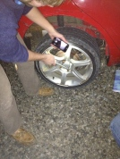 Loosening the nuts. Start with one, then do the one directly across from it. In this case there were four. To loosen, put the tire iron on the bolt and then kick it down (left loosey, righty tighty).