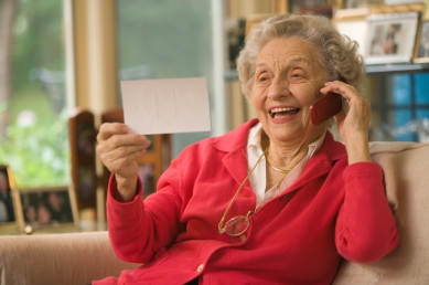 Senior looking at photograph and talking on cell phone