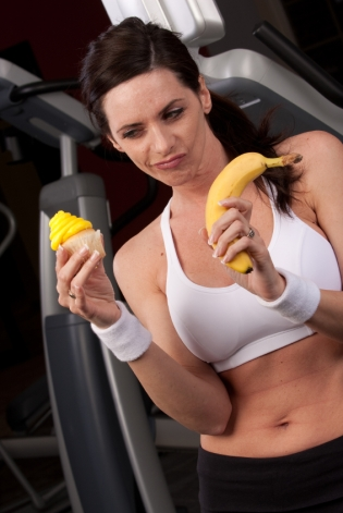 A woman handling the internal struggle to maintain and patriarchal norm of low body fat and pretending to find the banana and cupcake equal in taste.