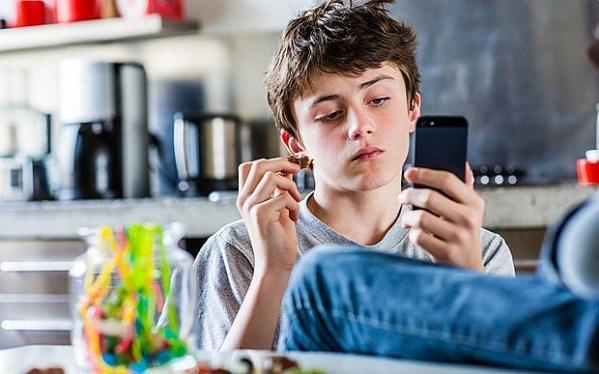 Teenage boy eating sweets.
